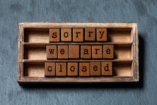 Sorry we are closed. Vintage box, wooden cubes message with old style letters. Gray stone background.