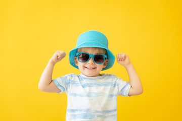 Portrait of happy child against yellow background. Summer vacation concept Wall mural