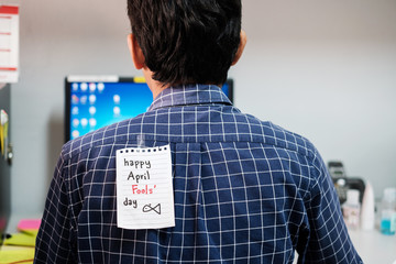 Back of young man office with a white paper note attached with the text happy april fools day