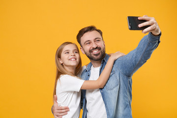 Bearded man in casual clothes with child baby girl. Father little kid daughter isolated on yellow background. Love family day parenthood childhood concept. Doing selfie shot on mobile phone, hugging.
