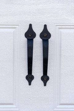 Elegant black powder coated spade lift handle pair on a raised panel white garage door