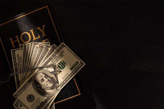 top view of holy bible with money and cross on dark background with sunlight