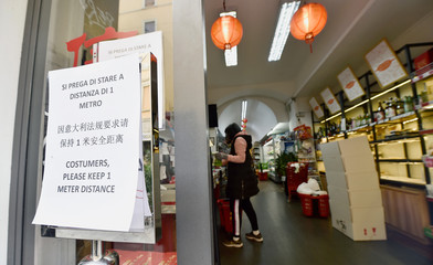 A sign advising customers to keep one meter distance is seen in front of a store, after a decree orders for the whole of Italy to be on lockdown in an unprecedented clampdown aimed at beating the coronavirus, in Milan