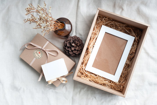 A white picture frame placed in a brown gift box surrounded by a box of small diamond rings tied with cream-colored pine cones dried flowers in a brown glass bottle. Put on a light brown fabric