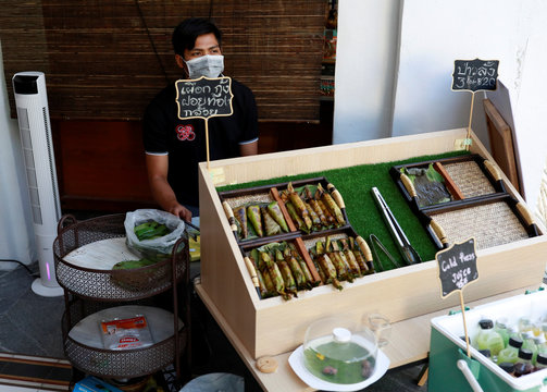 A vendor waits for customers at an empty tourist area, due to fear of the coronavirus in Phuket