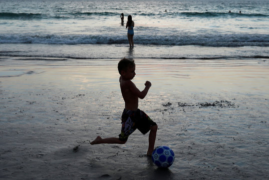 A child kicks a ball on a beach which is usually full of tourists, amid fear of coronavirus in Phuket