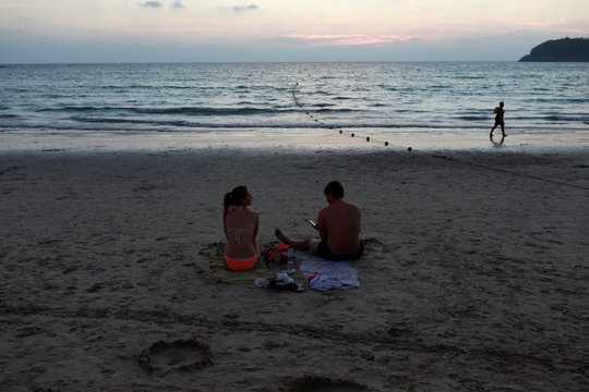 People sit on a beach which is usually full of tourists, amid fear of coronavirus in Phuket