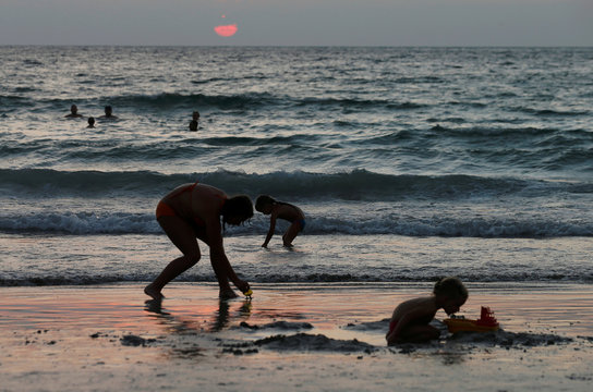 People are seen on a beach which is usually full of tourists, amid fear of coronavirus in Phuket