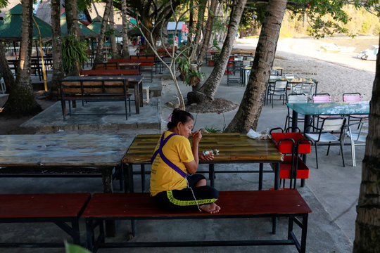 A woman sits near a beach which is usually full of tourists, amid fear of coronavirus in Phuket