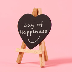 text day of happiness in a heart-shaped sign