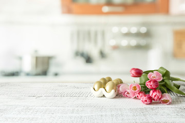 Easter eggs, tulips on kitchen white wooden table. Spring composition. Space for design.