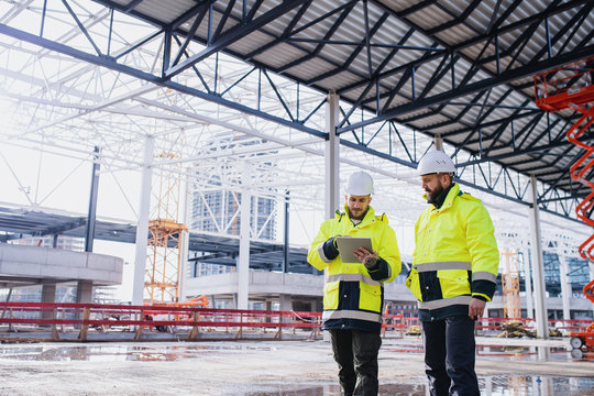 Men engineers standing outdoors on construction site, using tablet.