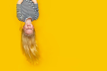 Excited crazy little blonde girl hanging happy upside down over isolated yellow studio background. Emotion, expression. Copy space for text. Fototapete
