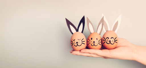 Three painted smiling Easter eggs bunnies on woman's hand