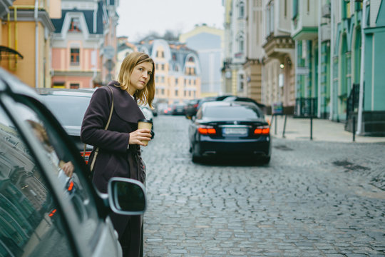 Stylish young woman crossing city streets with cup of coffee