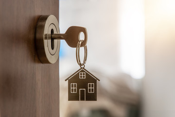 Obraz Open door to a new home with key and home shaped keychain. Mortgage, investment, real estate, property and new home concept - fototapety do salonu