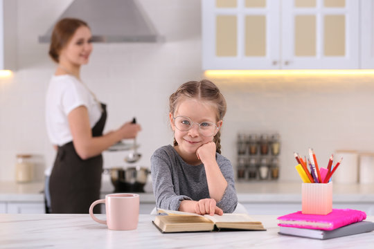 Little girl doing homework while mother cooking in kitchen