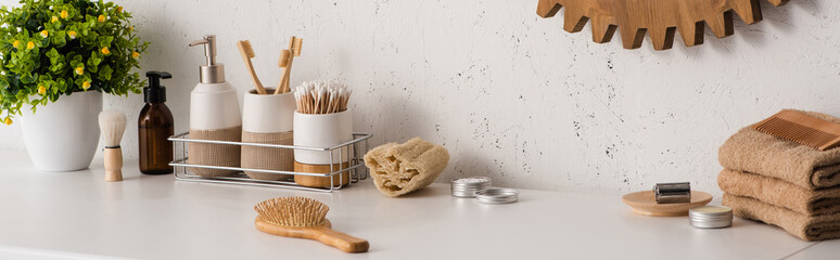 Panoramic view of shelf with hygiene objects and beauty products with flowerpot in bathroom, zero...