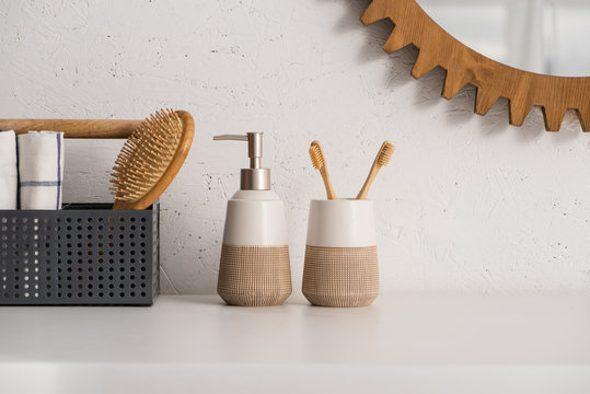 Box with hairbrush and towels near liquid soap and toothbrush holder with toothbrushes in bathroom, zero waste concept