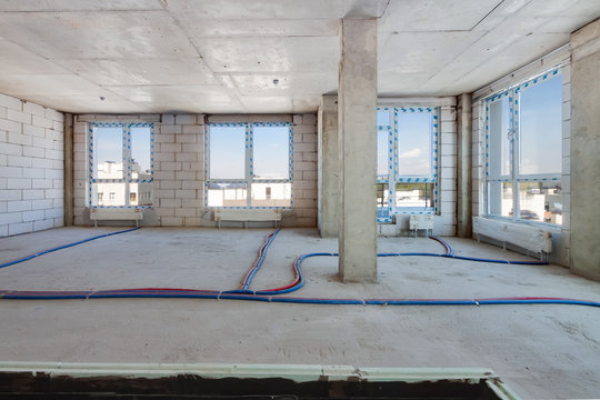 Construction site of residential apartment building interior in progress with panoramic windows and white brick wall light sunny day