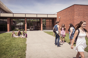School kids hanging out outside in front of the school . Red Lodge, Montana, USA