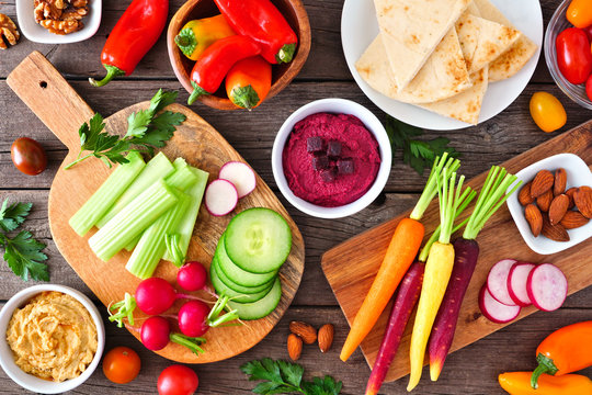 Table scene with a variety of fresh vegetables and hummus dips. Overhead view on a rustic wood background.