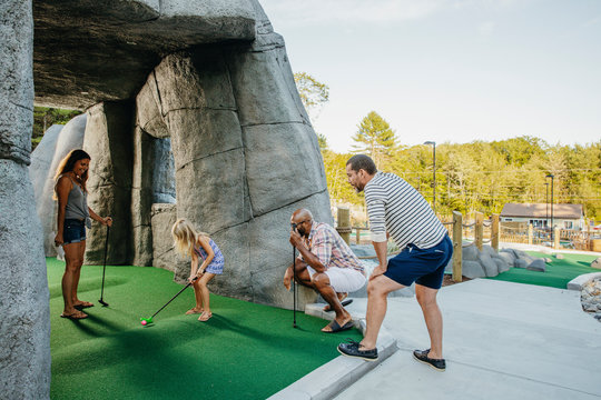 Mature men and woman looking at girl playing golf in miniature golf course