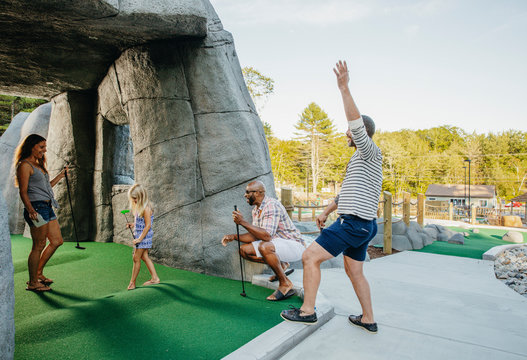 Family and friends cheering for girl taking winning shot at miniature golf course