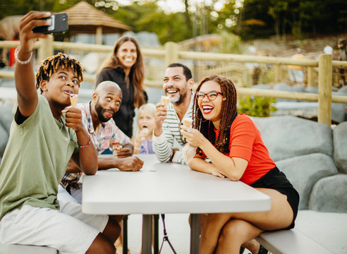 Teenage boy taking selfie with friends and family while having ice cream at golf course
