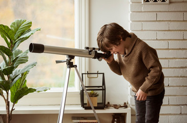 Side view of curious boy looking through telescope while standing by wall at home