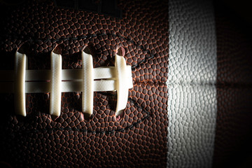 Close-up of an American football on black background
