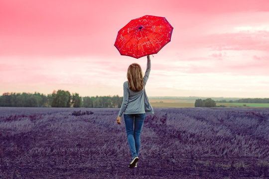 a girl stands with an umbrella in a field