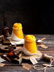 two glass jars with cold dessert (panna cotta, jelly, mousse, pudding) with orange and white layers on wooden boards on rustic table