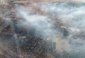 A view from an airplane window shows smoke rising from chimneys in Helwan's industrial zone in Cairo