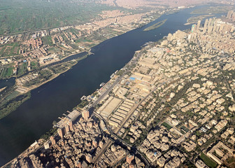 A view from an airplane window shows buildings around the Nile River in Cairo
