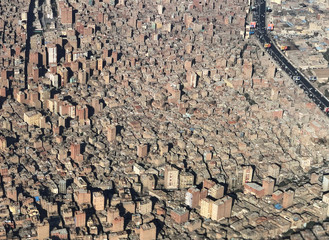 A view from an airplane window shows buildings in an area of dense population in Cairo