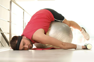 Lazy young man with exercise ball on yoga mat indoors