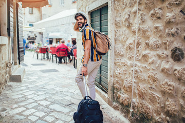 Handsome bearded tourist with backpack is making travel across city. Papier Peint