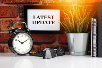 LATEST UPDATE text with alarm clock, books and vase on brick background. Business, Quotes and Copy Space concept