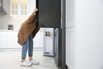 Young woman looking into refrigerator in kitchen