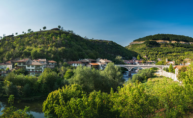 Stores à enrouleur Europe de l Est Panoramic view of Veliko Tarnovo from Tsarevets hill in summer. Typical Bulgarian town in Eastern Europe, river landscape, bridge and terrace architecture in Veliko Tarnovo, Bulgaria.