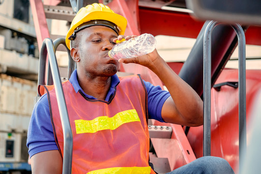 Portrait of African worker man drink water from bottle and stay on big crane truck in cargo shipping area.