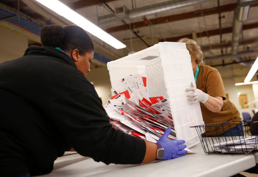 Workers empty a carton of ballots from a drop box to prepare them for the mail sorting machine during the presidential primary at King County Elections ballot processing center in Renton