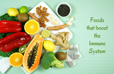Foods that boost the Immune System. Citrus, red bell peppers, broccoli, garlic, ginger, spinach, almonds, turmeric, green tea, papaya, kiwi fruit, poultry and sunflower seeds. Text title heading.