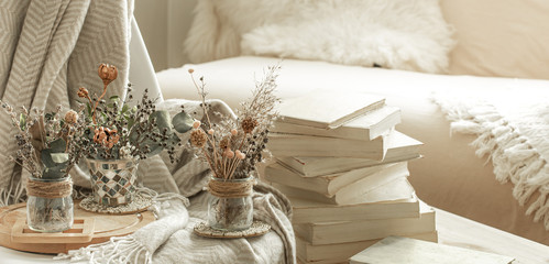 Home interior with books and dried flowers.