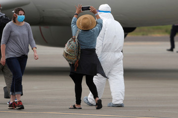 A passenger from the cruise ship Grand Princess takes a photograph on the tarmac at Oakland International Airport as authorities continue debarkation from the ship after 21 people on board have tested positive for the COVID-19 coronavirus in Oakland
