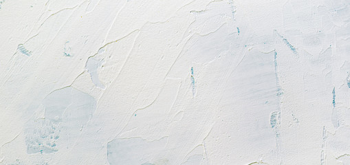 Old looking white wall texture with white plaster stucco and spatula strokes. Faint blue paint under the plaster surface. Textured wallpaper or background image.
