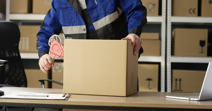 Close up of hands of Caucasian postal male worker in uniform packing carton box at delievery department in post office. Postman closing parcel with sticky tape. Mail shipping concept.