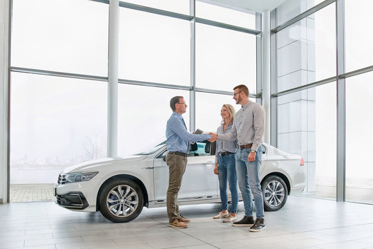 Sales manager helping young couple  choose a new car and shaking hands after a successful car buying in modern car showroom