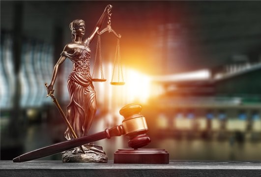 Statue of the lady of justice with scales and gavel on the desk